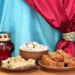 東洋のお菓子 - シャーベット、ハルヴァ、カーテンのクローズ アップの背景に木製のテーブルにトルコ語ディライトとソーサー — ストック写真 #11473185