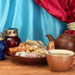 Teapot with cup and plate with oriental sweets - sherbet, halva and turkish delight on wooden table on a background of curtain close-up - Stock Photo