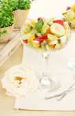 Fresh fruits salad and strawberries on wooden table — Stock Photo
