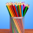 Color pencils in glass on wooden table on blue background - Stock Photo