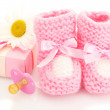 Постер, плакат: Pink baby boots pacifier gift and flower isolated on white