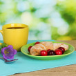 Croissant with cherries and coffee on wooden table on green background — Stock Photo #11483224