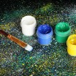 Jars with colorful gouache and brush on black background, spattered with colorful paint close-up — Stockfoto