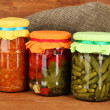 Stock Photo: Jars with canned vegetables on wooden background close-up