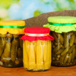 Jars with canned vegetables on green background close-up — Stock Photo #11484532