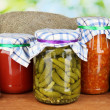 Jars with canned vegetables on green background close-up — Stock Photo #11484536