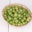 Green gooseberry in basket on wooden background - Stock Photo