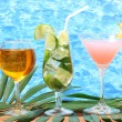 Glasses of cocktails on wooden table on blue sea background - Stock Photo