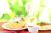 Composition of delicious cooked spaghetti with tomato sauce on bright colorful background — Stock Photo