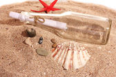 Glass bottle with note on sand shore with seashells — Stock Photo