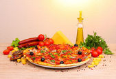 Delicious pizza, vegetables and salami on wooden table — Stock Photo