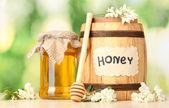 Sladký med v sudu a jar s květy akátu na dřevěný stůl na zeleném pozadí — Stock fotografie