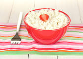 Cottage cheese with strawberry in red bowl and fork on colorful napkin on white wooden table close-up — Stock Photo