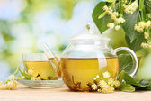 Teapot and cup with linden tea and flowers on wooden table in garden — Stock Photo