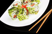 Tasty rolls served on white plate with chopsticks isolated on black — Stock Photo