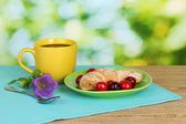 Croissant with cherries and coffee on wooden table on green background — Foto de Stock