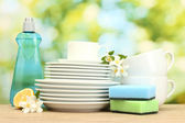 Empty clean plates and cups with dishwashing liquid, sponges and lemon on wooden table on green background — Stock Photo