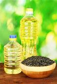 Aceite de girasol en botellas con semillas de girasol en primer plano de fondo verde — Foto de Stock