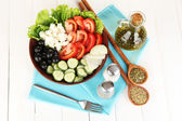 Tasty Greek salad with spices on white wooden background — Stock Photo