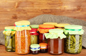 Jars with canned vegetables and fruit on wooden background close-up — Stock Photo