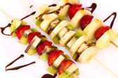 Mixed fruits and berries on skewers with chocolate close-up — Stock Photo