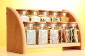 在黄色背景上的木架子上的玻璃罐子粉香料 — 图库照片