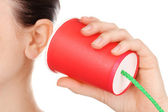 Human ear and paper cup near it close-up isolated on white — Stock Photo