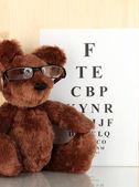 Oso de peluche con gafas de vista prueba primer plano de fondo de tabla — Foto de Stock