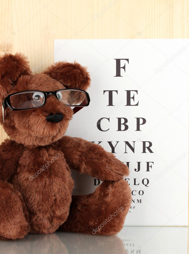 Teddy bear with glasses on eyesight test chart background close-up — Stock Photo #11485130