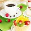 Cup of coffee and sweet cakes with fruits on wooden table - Stock Photo