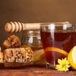 Honig, Zitrone, Waben und einer Tasse Tee auf Holztisch auf braunen Hintergrund — Stockfoto