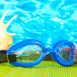 Blue swim goggles with drops on a bamboo pad, on blue sea background — Stock Photo