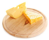 Cheese on cutting board isolated on white — Stock Photo