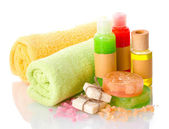 Bottles, soaps, sea salt and towels isolated on white — Stock Photo