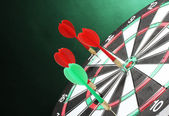 Dart board with darts on green background — Stockfoto