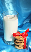 Glass of milk and cookies on blue cloth background — Stock Photo