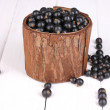 Black currant in wooden cup on wooden background — Stock Photo #11507741