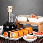lahodné sushi na desku, hůlky, sójová omáčka, ryby a krevety na bambusové rohoži na šedém pozadí — Stockfoto #11507819