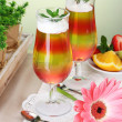 Stock Photo: Fruit jelly in glasses and fruits on table in cafe