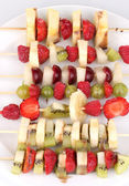 Mixed fruits and berries on skewers close-up — Stock Photo