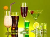 A variety of alcoholic drinks on green background — Stock Photo