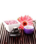 Composição de pedras spa, banho de sal, vela e gerbera na esteira de bambu no fundo branco — Foto Stock