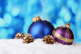 Beautiful blue and purple Christmas balls and cones in snow on blue background — Stock Photo