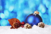 Beautiful blue Christmas ball and branch on snow on blue background — Stock Photo