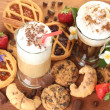 Glasses of coffee cocktail on wooden table with sweet and flowers — Stock Photo #11511312