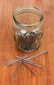 Metal nails and glass jar on wooden background — Stockfoto