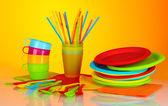 Vajilla desechable plástico brillante en colores de fondo — Foto de Stock