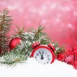 Green Christmas tree with toy and clock in the snow on red — Stock Photo #11522906