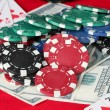 Stock Photo: The red poker table with playing cards, poker chips and dollars