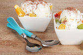 Delicioso helado de vainilla con chocolate y frutas en cuencos y cucharas sobre fondo de madera — Foto de Stock
